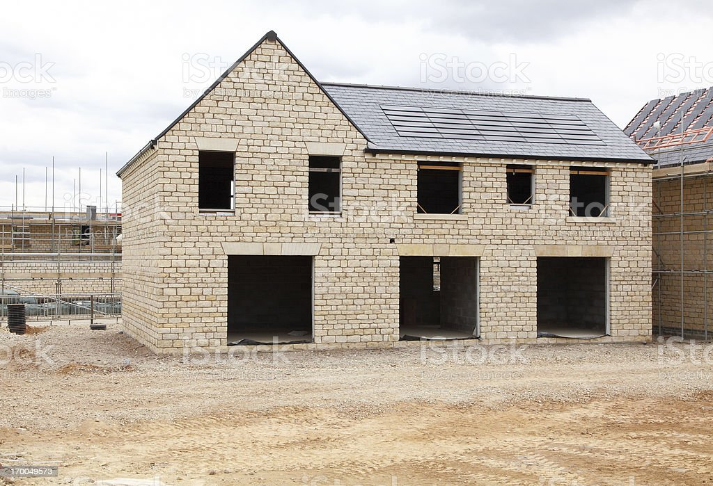 A large house under construction with modern solar panels on the roof.
