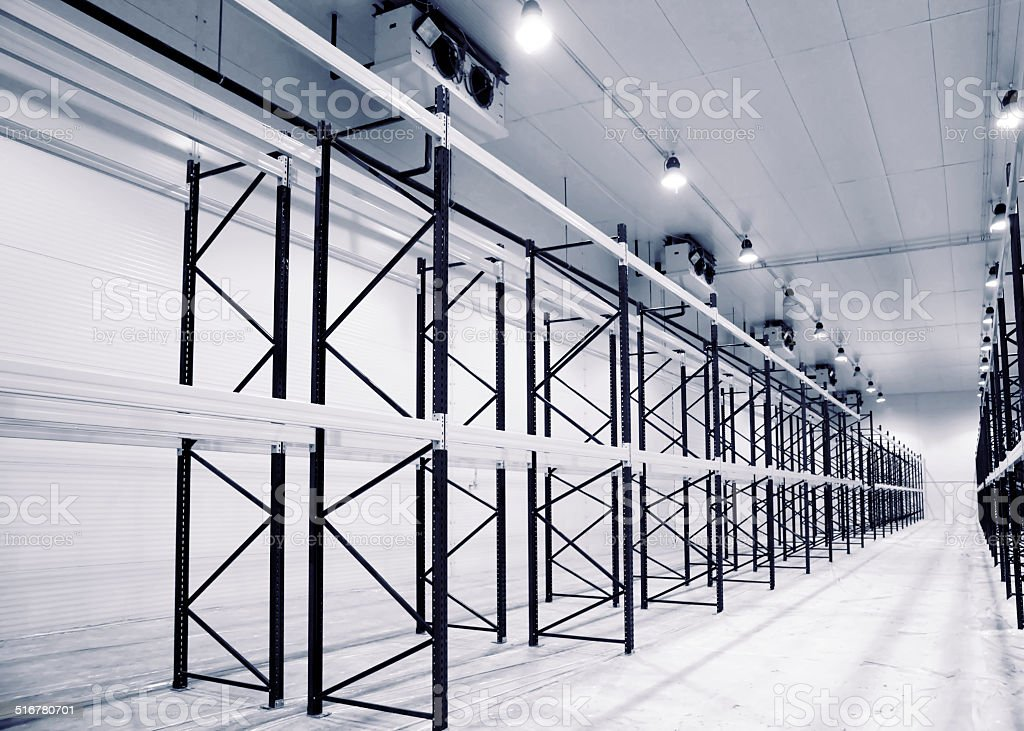 Large newly built warehouse with steel shelves, toned