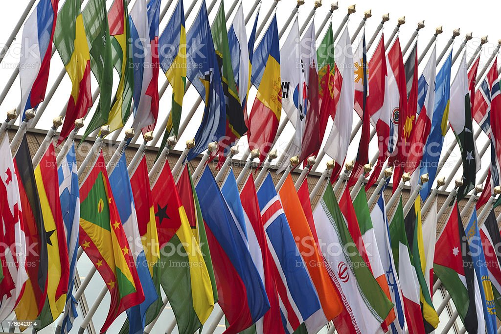 large number of national flags flying stock photo