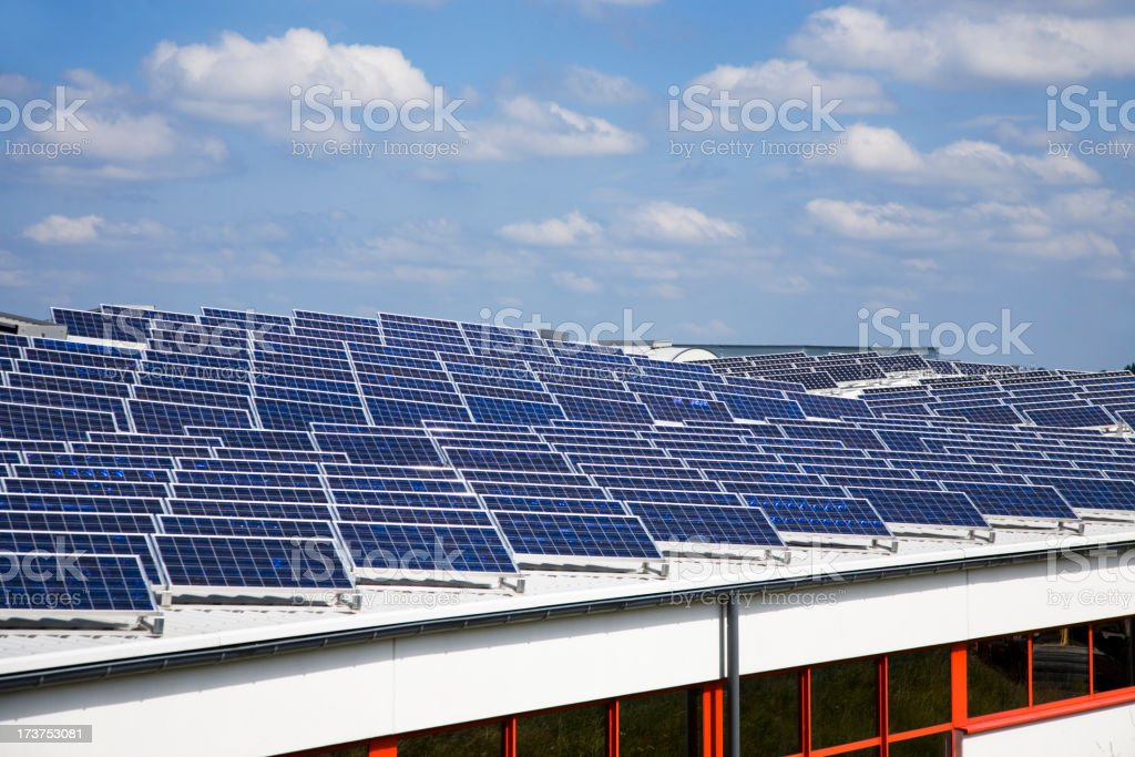 Large number of Solar panels on rooftop under a blue sky royalty-free stock photo