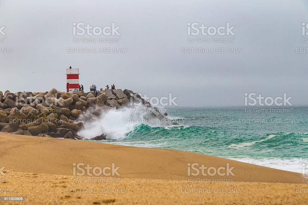 Large ocean waves crushing pier with lighthouse in Nazare, Portugal stock photo