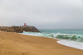 Large ocean waves crushing pier with lighthouse in Nazare, Portugal