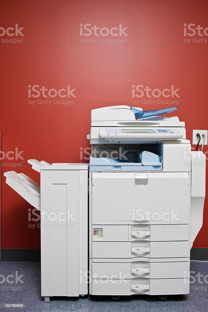 Large office photocopier in front of red wall stock photo