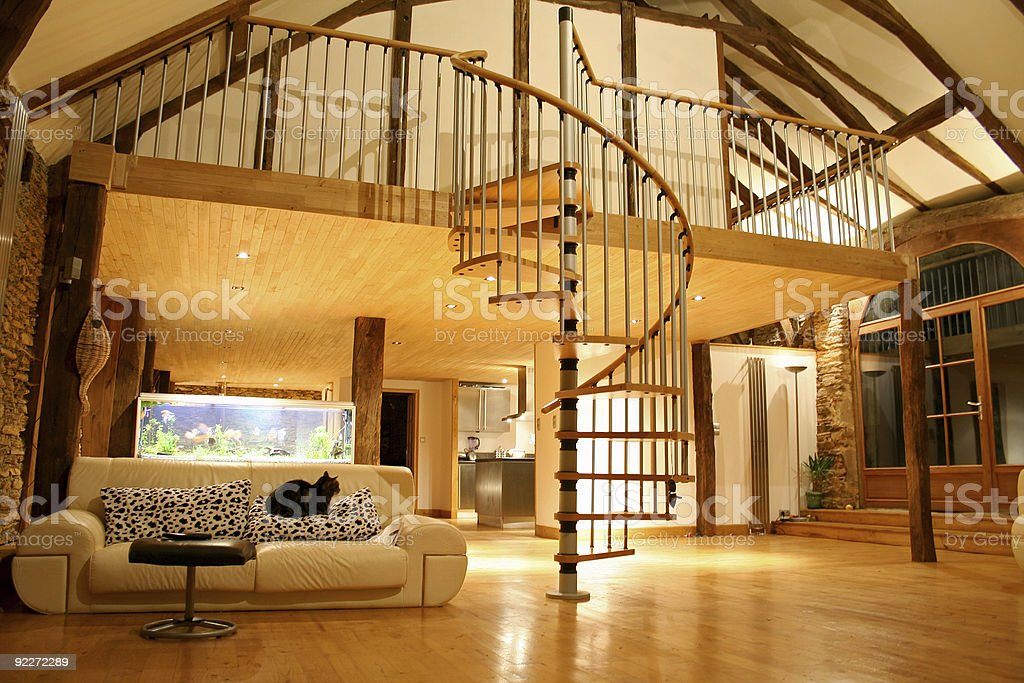 Large open living area with spiral staircase up to a loft stock photo