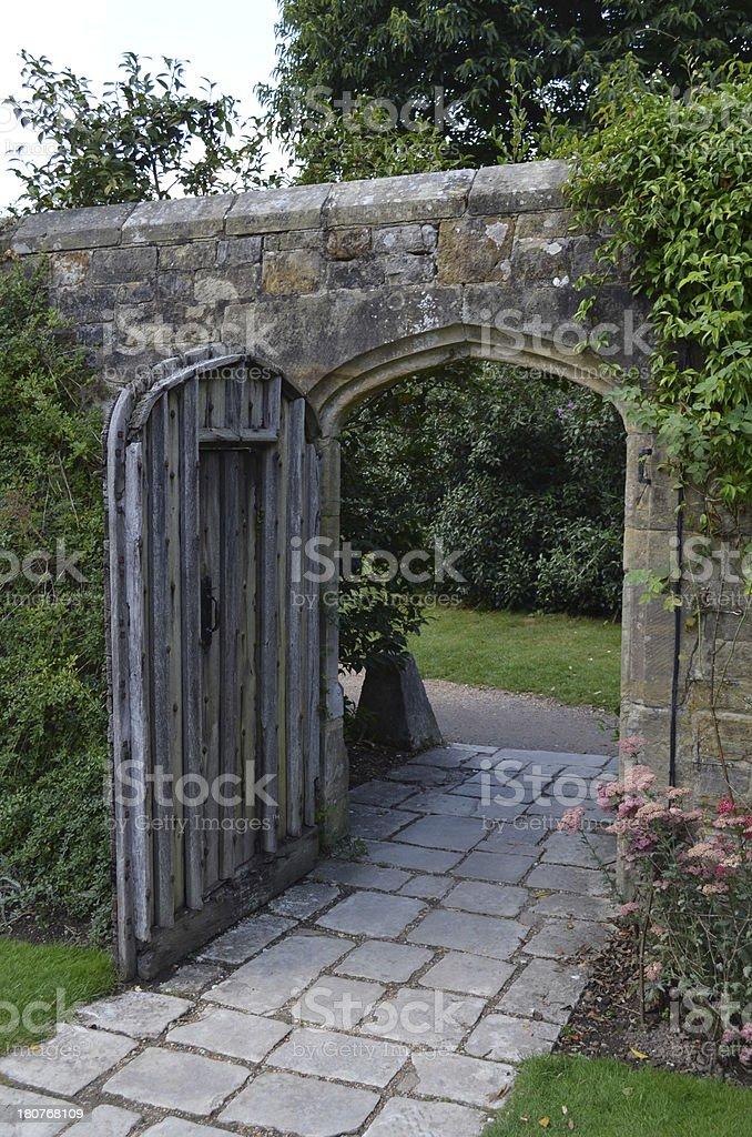 Large open wooden door in pretty garden. royalty-free stock photo