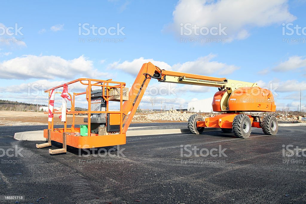 Large, orange boom lift under a cloudy sky royalty-free stock photo