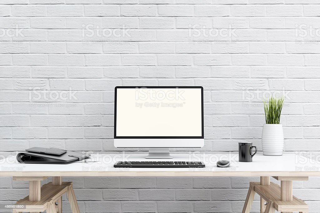 Large PC moniror in front of a brick wall stock photo