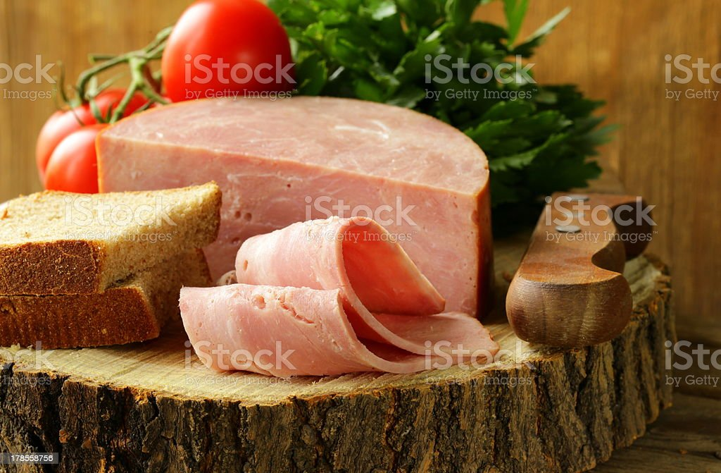 large piece of ham on a cutting board royalty-free stock photo