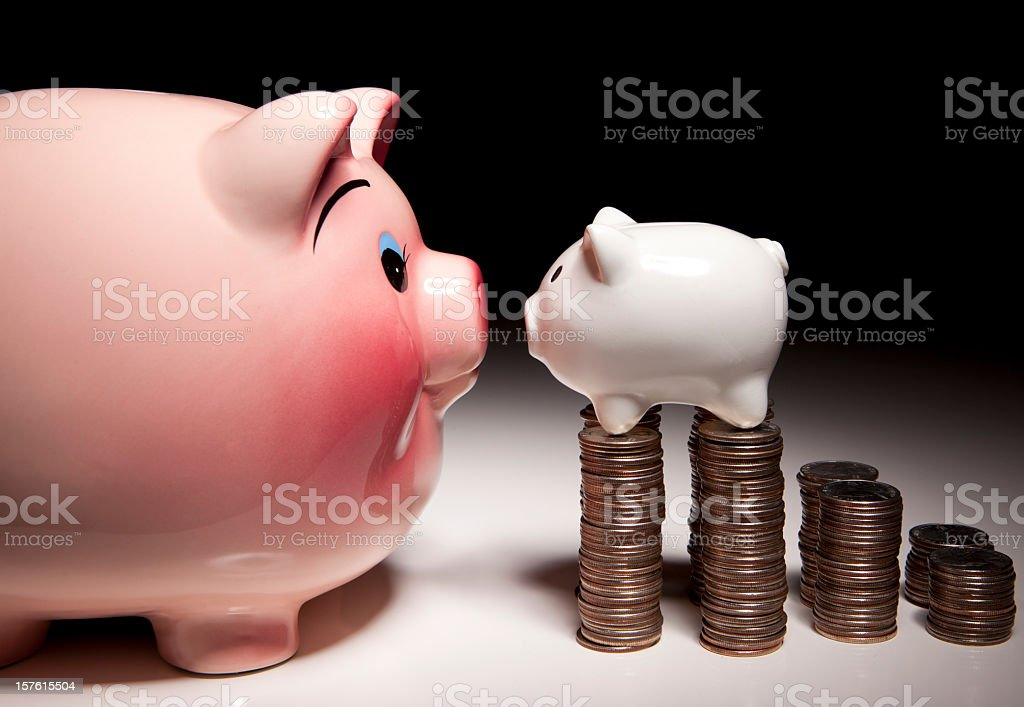Large piggy bank facing small pig on a stack of quarters royalty-free stock photo