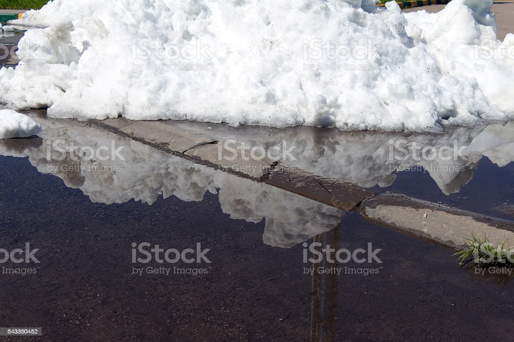 Large pile of dirty snow (ice) lies in the summer stock photo
