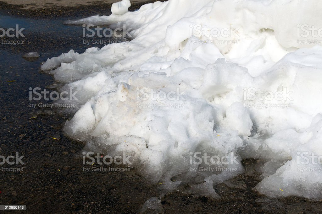 Large pile of dirty white snow lies on the stock photo