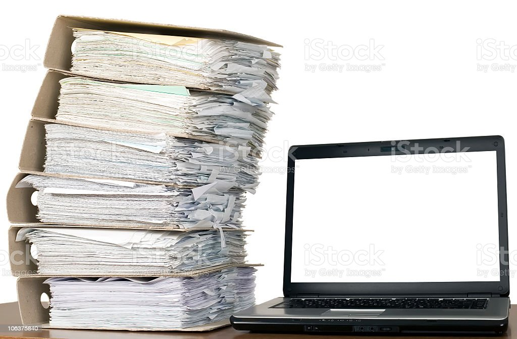 Large pile of documents next to a laptop stock photo