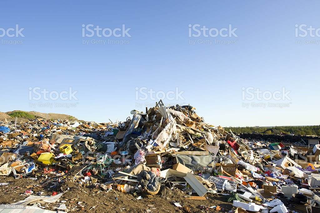 Large pile of garbage at a landfill with blue sky. stock photo
