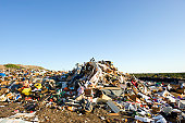 Large pile of garbage at a landfill with blue sky.