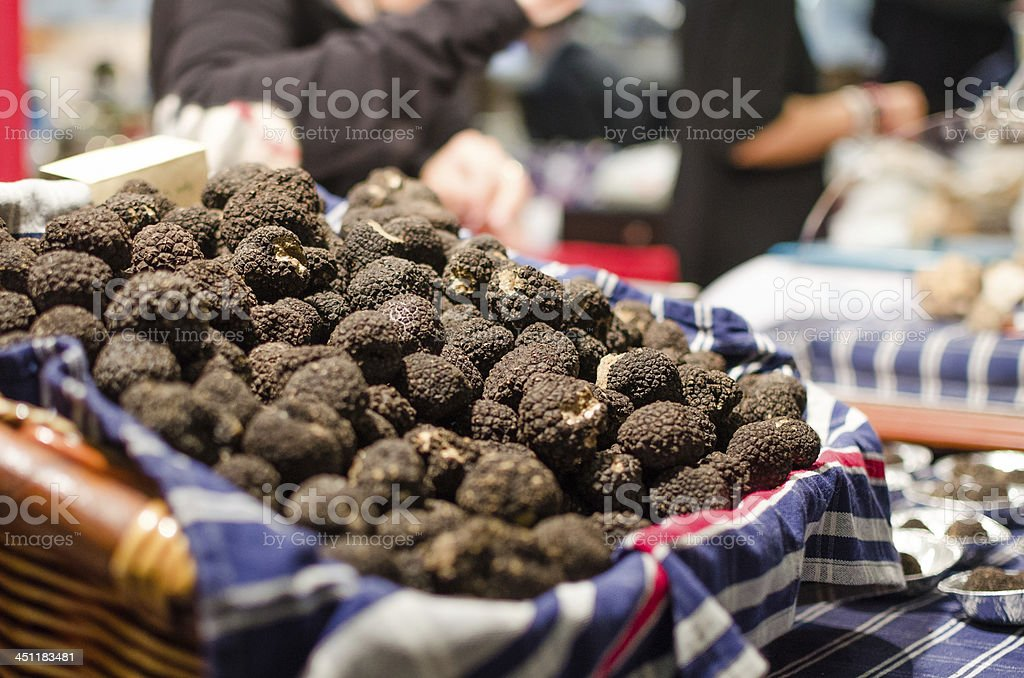 A large pile of truffles in a lined basket on a blue table stock photo