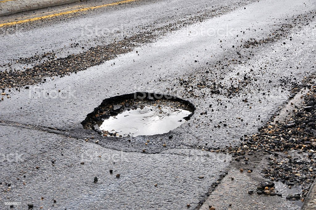 A large pot hole filled with water on an asphalt road stock photo
