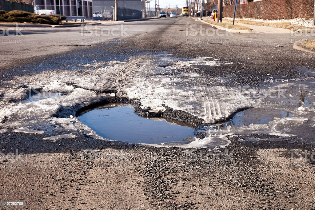 Large pothole with water and ice in the road stock photo