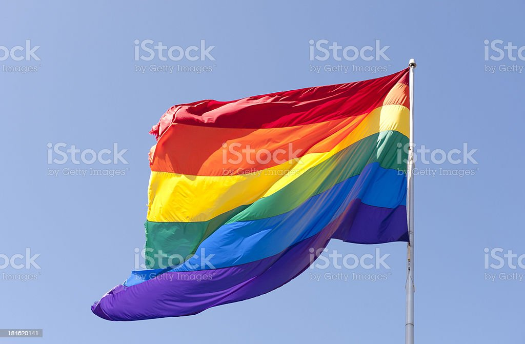 Large Rainbow Flag with blue sky stock photo