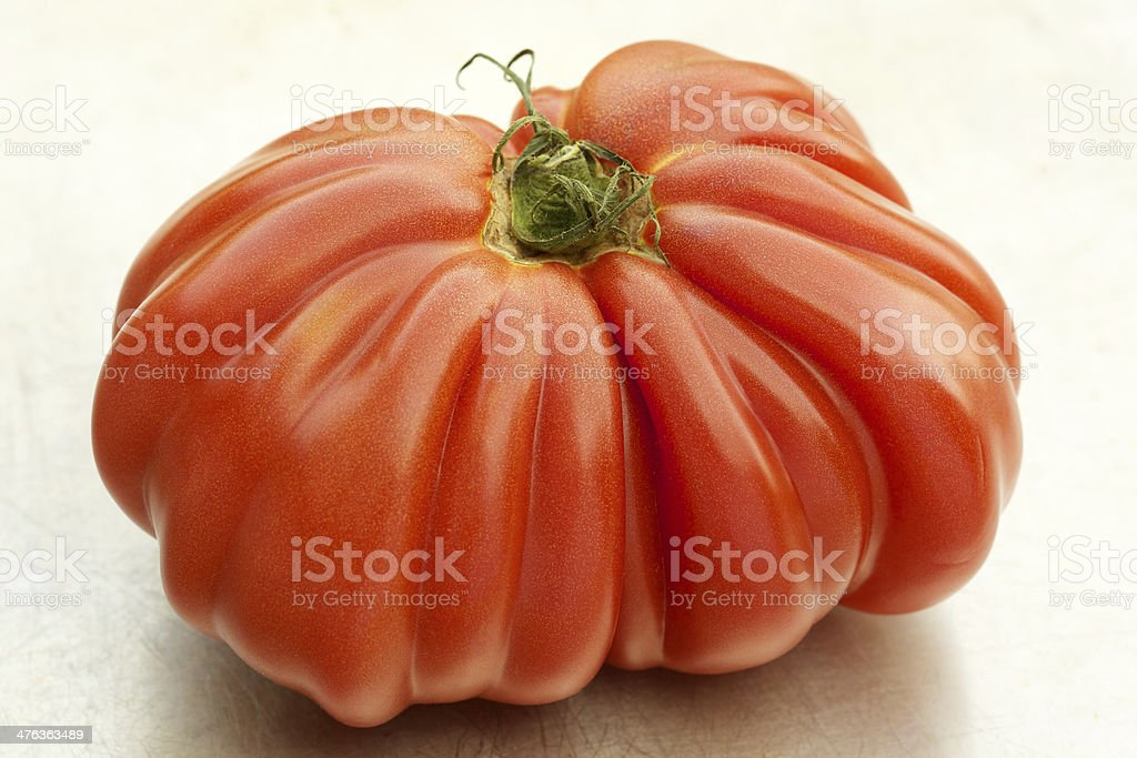 Large raw heirloom tomato on scratched metal royalty-free stock photo