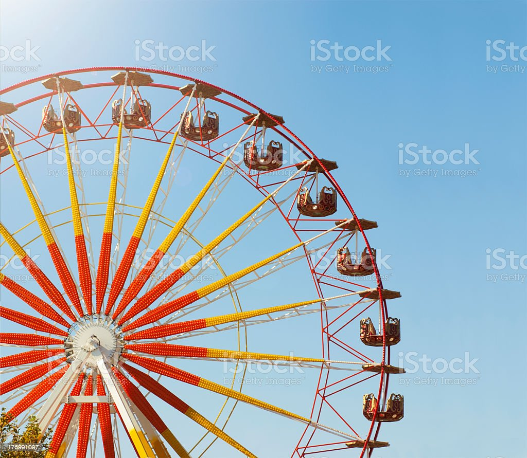 Large red and yellow Ferris wheel at a fair under a blue sky stock photo
