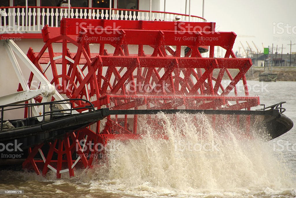 Large red paddle wheel in motion in a body of water stock photo