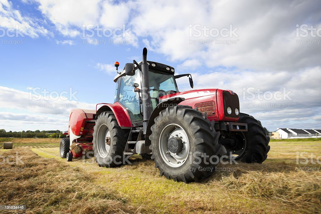 Large, red tractor gathering hay to make haystacks stock photo