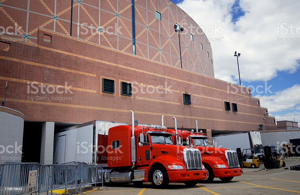 2 large red trucks parked outside a brick building stock photo