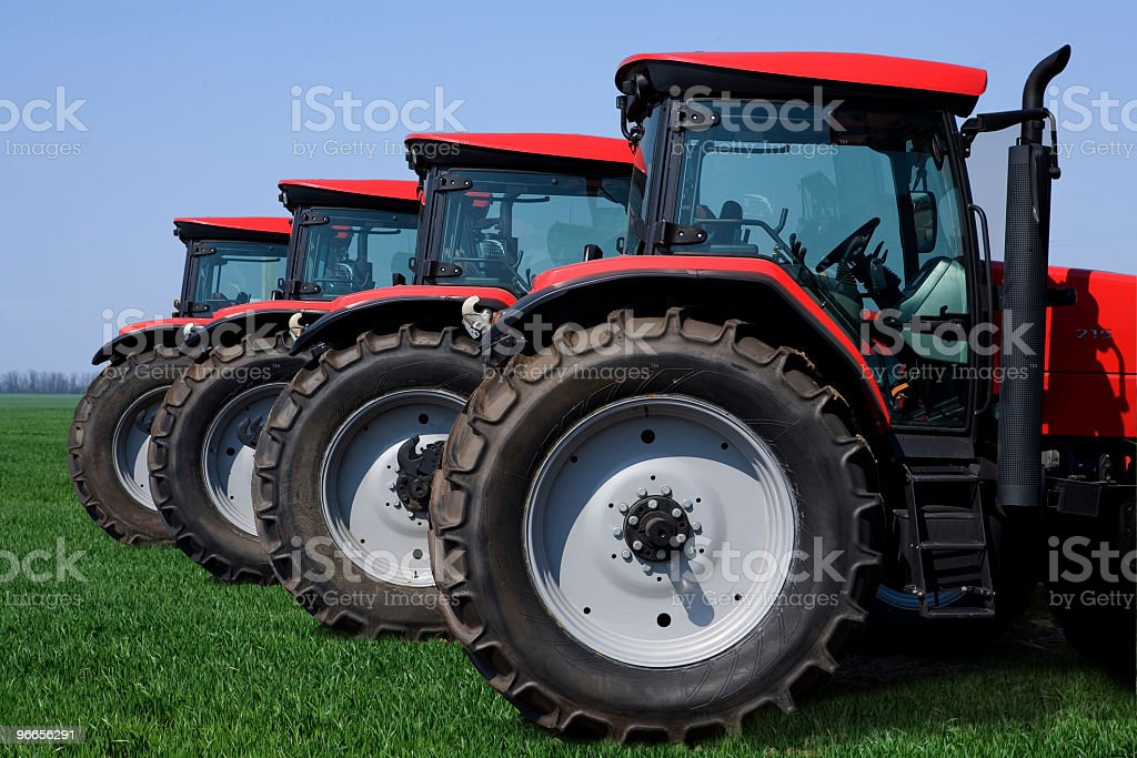 4 large red wheeled tractors in a row stock photo