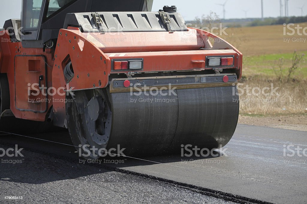 Large road-roller paving a road. Road construction stock photo