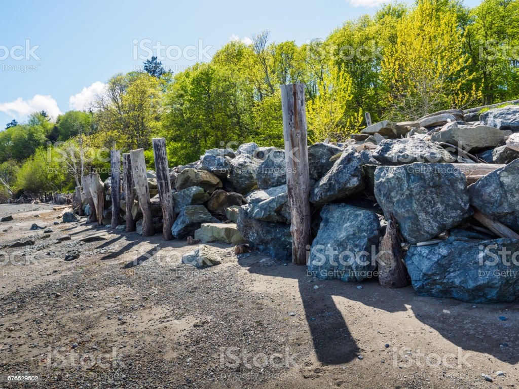 Large rocks piled to form retaining wall on the beach stock photo