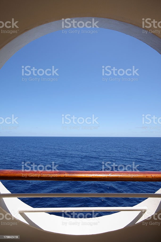 Large round porthole showing a deep blue sea outside royalty-free stock photo