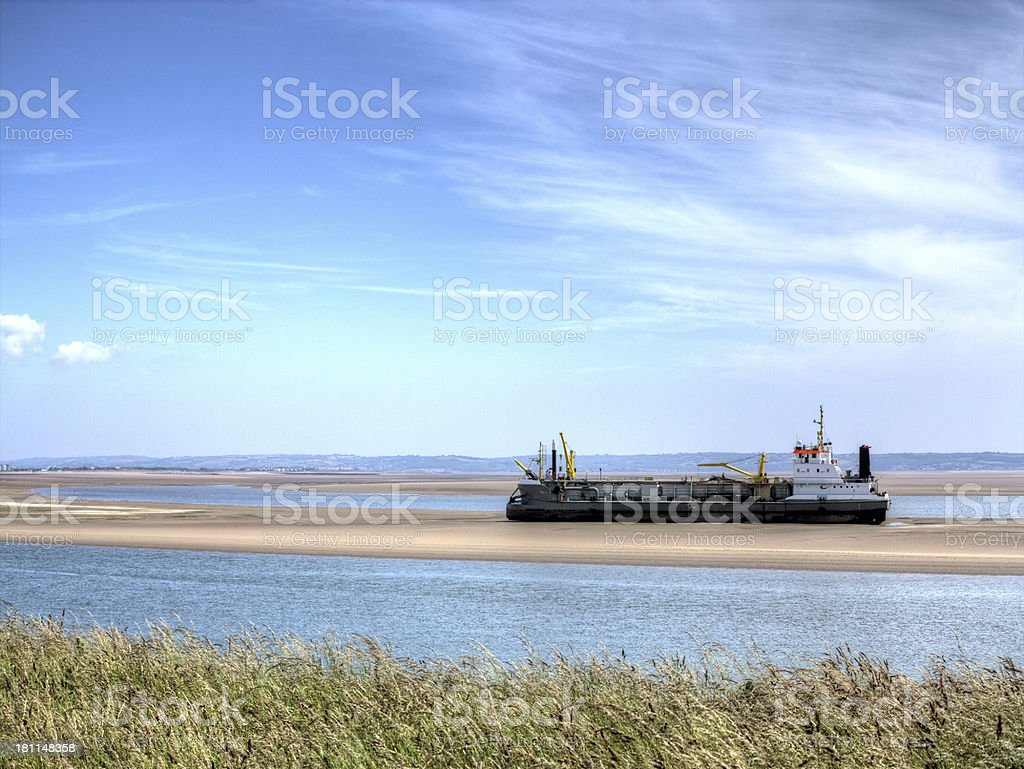 Large sand dredging boat moored on a sandbank royalty-free stock photo