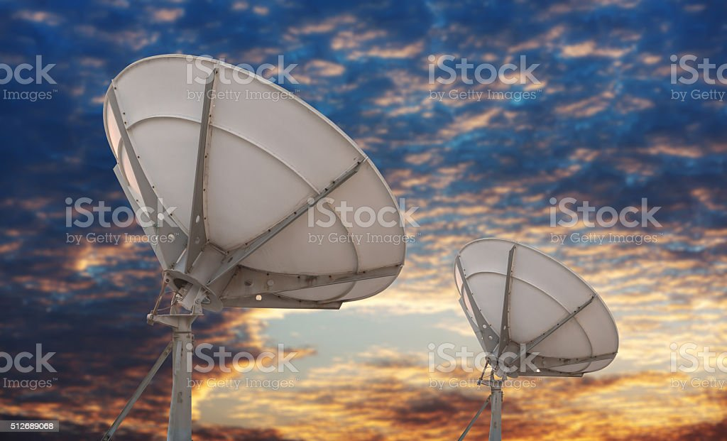 Large satellite antenna under twilight sky background stock photo