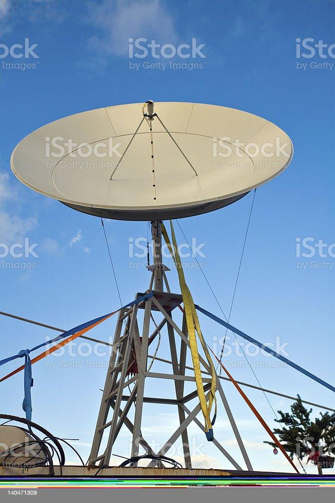 Large satellite dish against blue sky background stock photo