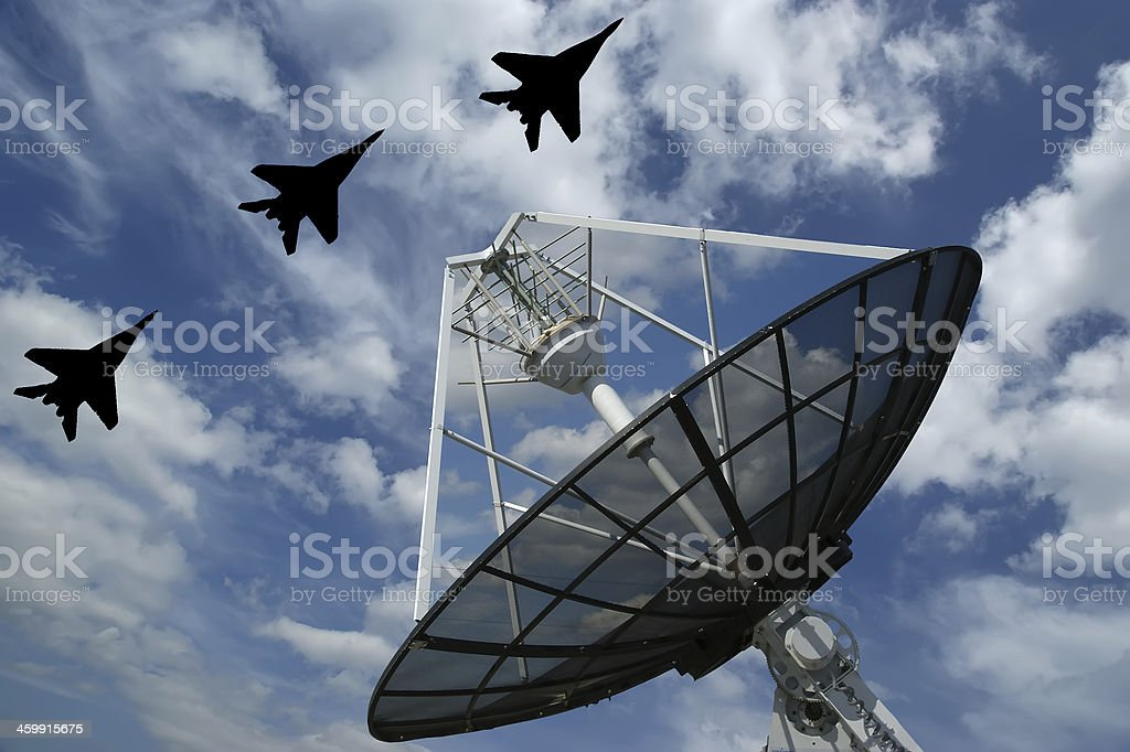 A large satellite radar flown over by three fighter jets stock photo