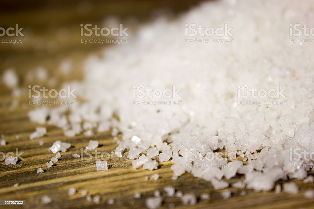 Large sea salt on wooden background stock photo