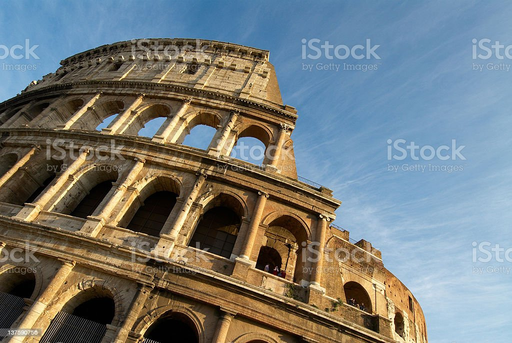 A large section of the colosseum among blue sky stock photo