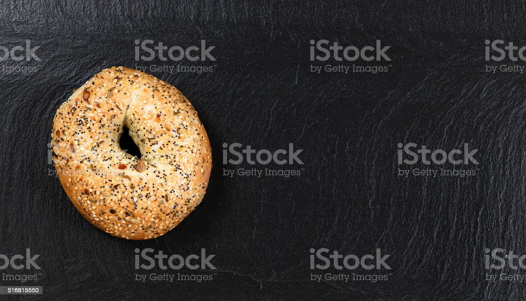 Large seeded bagel on natural slate stone background stock photo