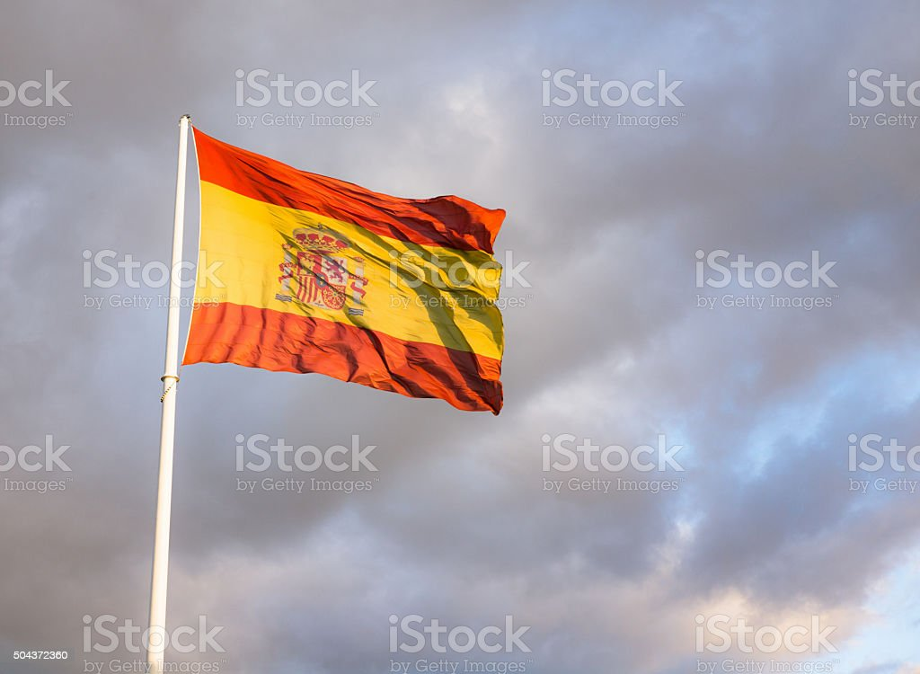 Large Spanish flag against overcast sky stock photo