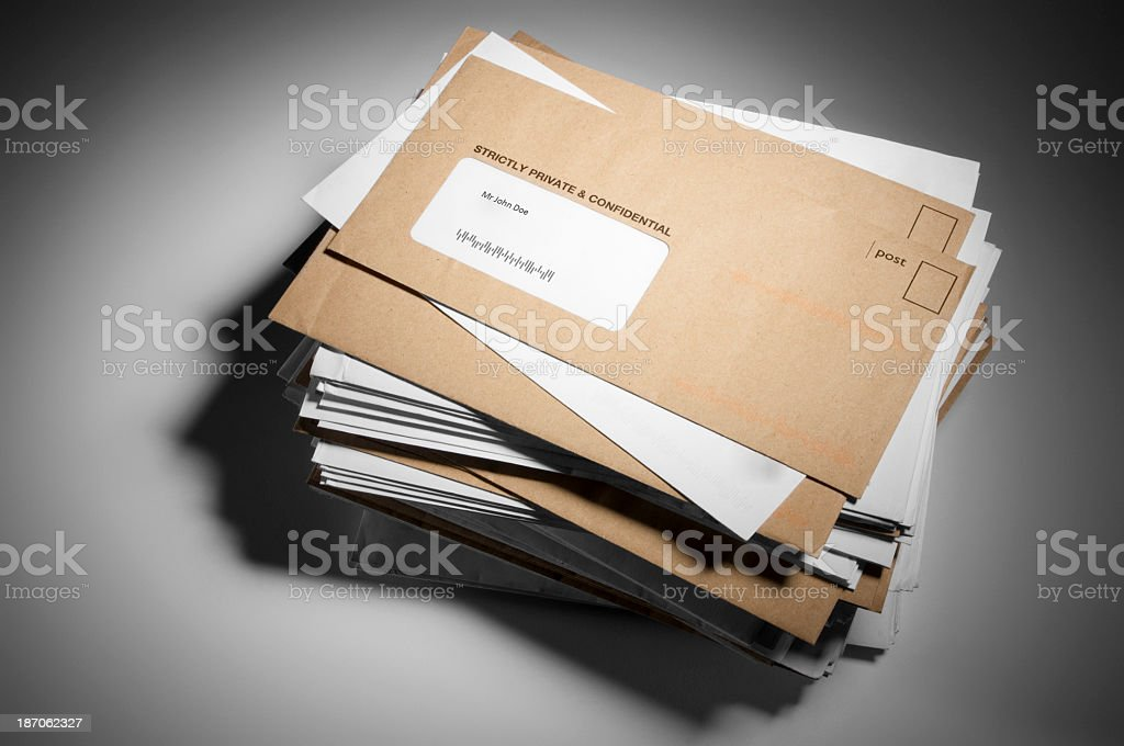 Large stack of brown and white mail on a gray background stock photo
