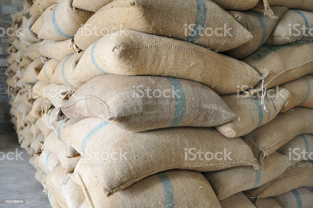 Large stack of closed coffee sacks stock photo