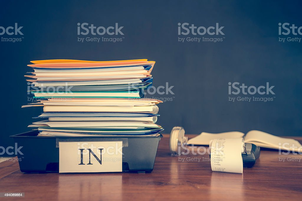 Large stack of paperwork and files with calculator. stock photo