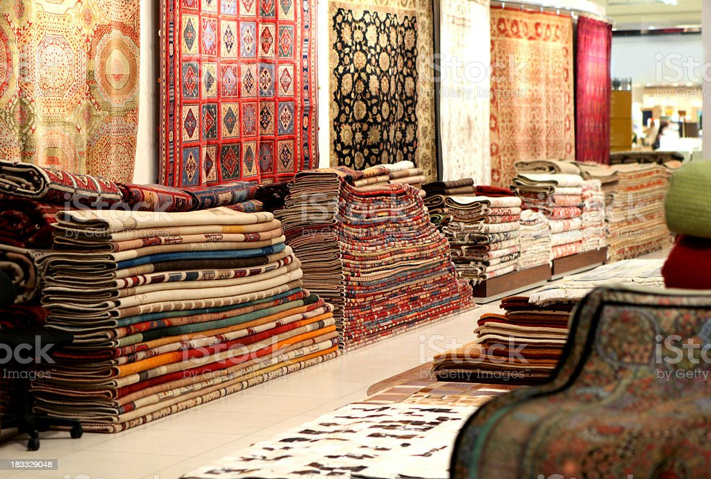 Large stacks of oriental Persian rugs in a store stock photo