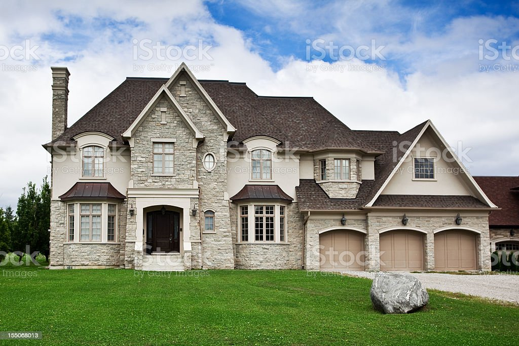 Large stone home with green lawn under blue sky stock photo
