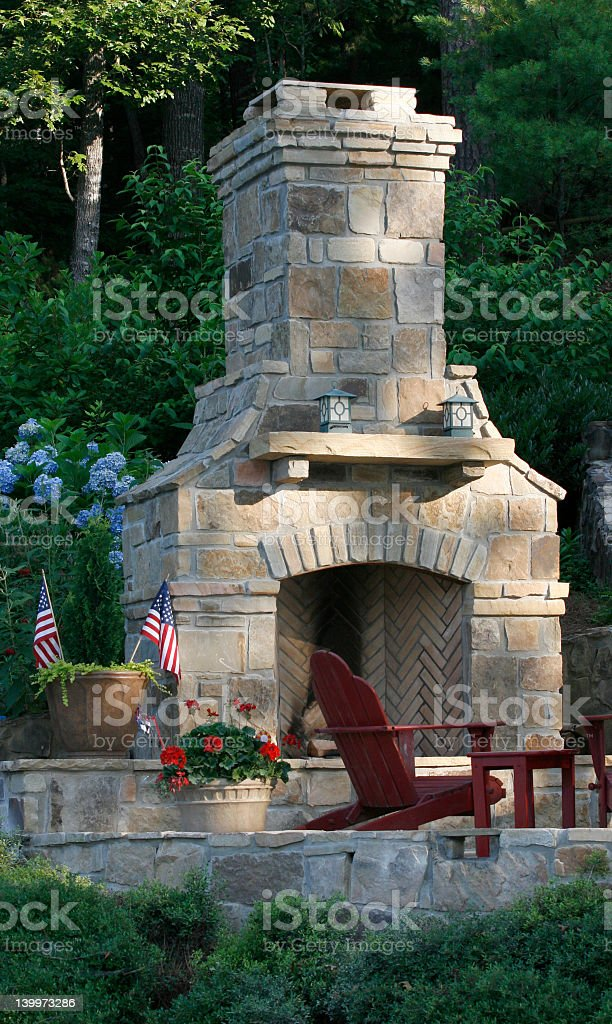 Large stone outdoor fireplace in garden stock photo