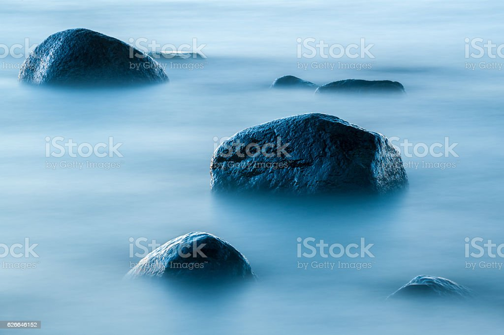 Large stones in the blue water stock photo