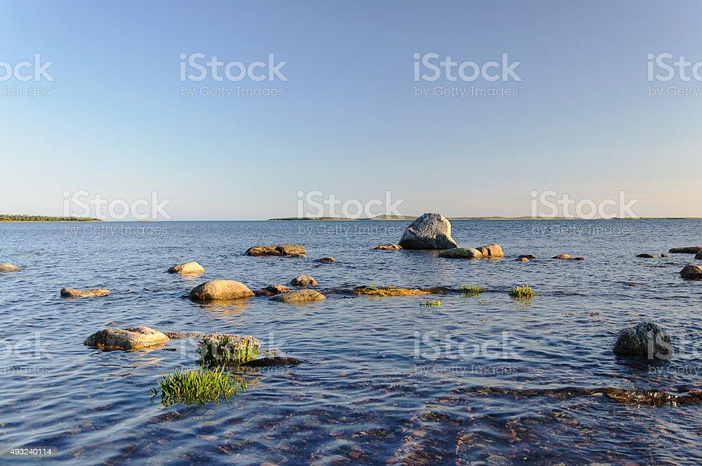 Large stones on seashore, sunset stock photo
