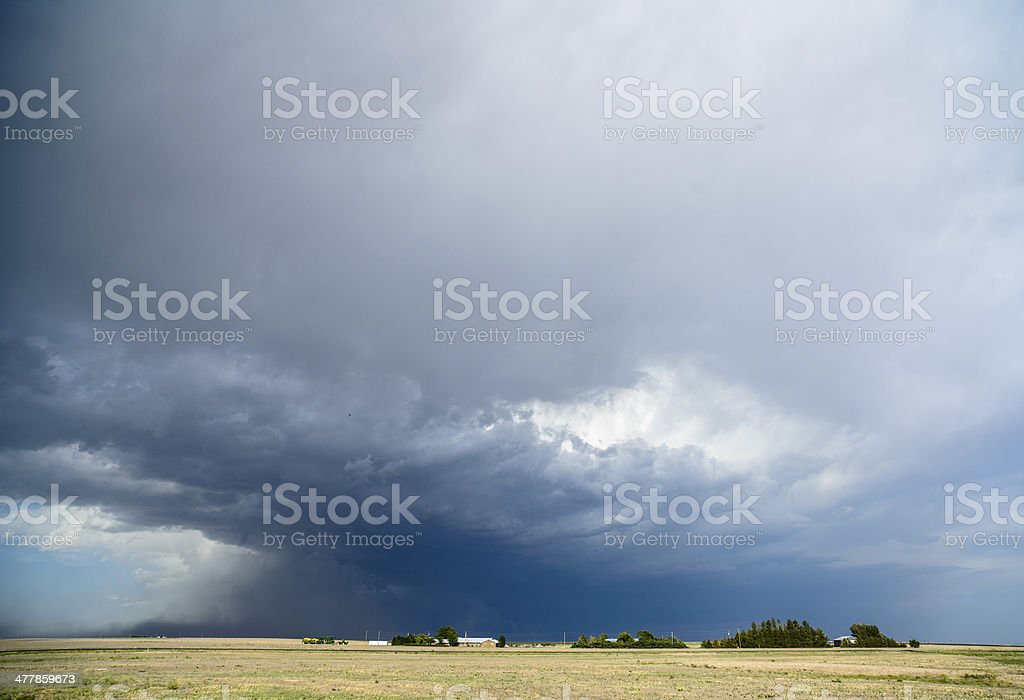 Large storm clouds build over dwarfed farms (XXXL) royalty-free stock photo