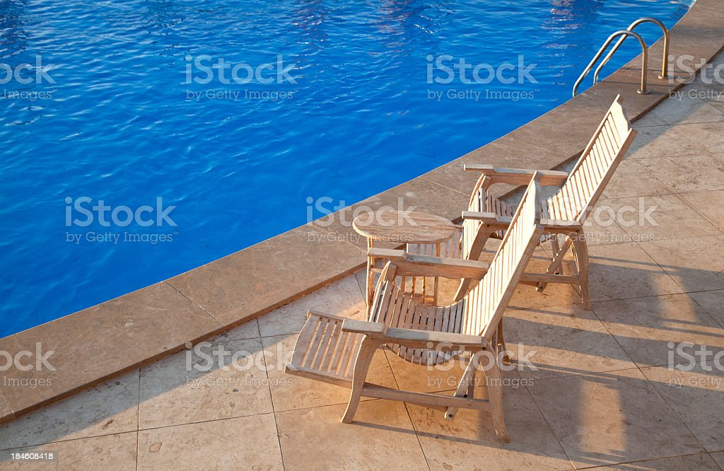 Large swimming pool with two wooden chairs near the edge stock photo