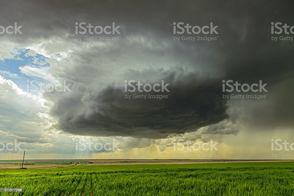 Large threatening thunderstorm rotates over cultivated farmland stock photo
